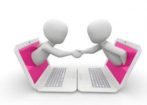 Zwei Menschen reichen sich durch ihre Laptopmonitore die Hände